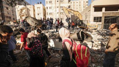 Palestinier på flykt från sina hem vandrade förbi husruiner i Gaza City på söndagen.