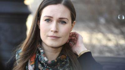 Sanna Marin drar sitt hår bakom örat med ena handen och tittar åt sidan.
