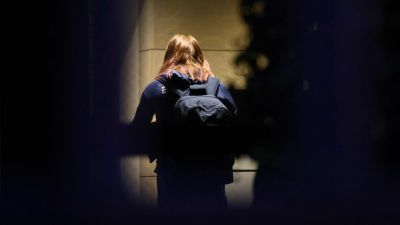 En kvinnas ryggtavla fotograferat genom ett fönster.