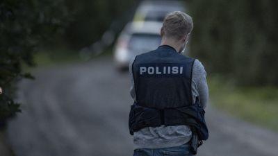 """En polis med ryggen mot kameran står på en grusväg. Polisen har en väst på sig. Det står """"poliisi"""" på ryggen."""