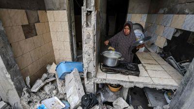 En palestinsk kvinna lagar mat i det som kvarstår av hennes hem i Gaza City efter de israeliska bombattackerna