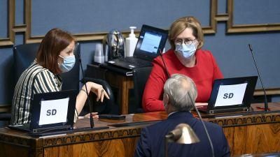 Riksdagsledamöter diskuterar med varandra i riksdagshuset