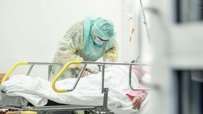Vårdpersonal i skyddsutrustning sköter en patient.