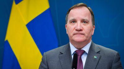 Stefan Löfven med allvarlig min och svenska flaggan i bakgrunden.