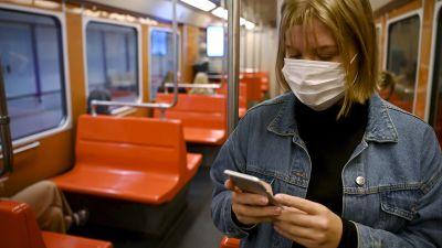 En person med ansiktsskydd i Helsingfors metro.