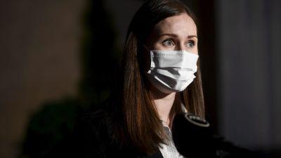 En kvinna i munskydd står i mörkret.
