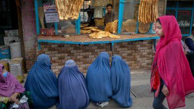 En man säljer bröd genom en liten lucka. Kvinnor klädda i blått sitter på trottoaren framför och en kvinna vandrar förbi.