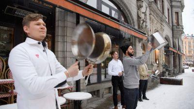 Krogpersonal i vita köksrockar slår på kastruller och grytlock utanför restaurang.