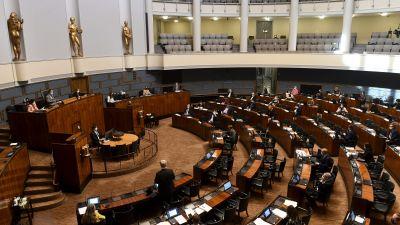 I en stor sal står bord och stolar på rad i en cirkel. Några människor sitter framme vid podium. Salen är smyckad med tre stora figurer i guld.