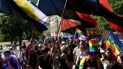 prideparaden där demonstranter viftar med stora flaggor.