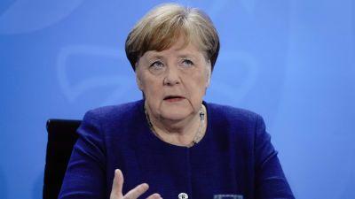 Merkel sitter och gestikulerar med händerna.