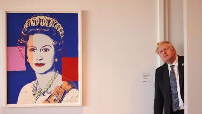 Boris Johnson kikar in genom en dörr och sneglar upp mot taket. Bredvid honom ett stort porträtt på drottning Elizabeth.