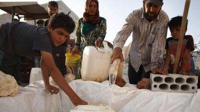 Syrier som är på flykt i inne i Syrien fyller kanistrar med vatten.