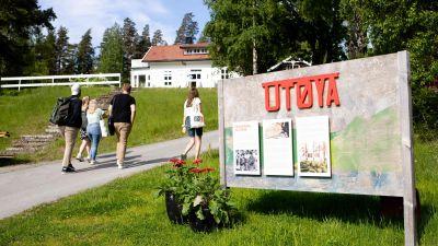 En Utoyaskylt på Utoya. I bakgrunden syns tre unga sommarklädda personer som går längs med en väg mot ett vitt hus.