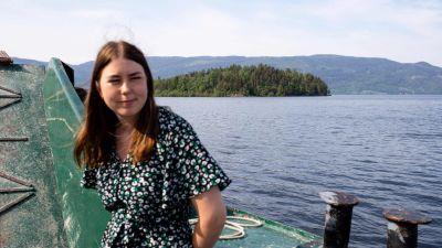 Astrid Eide Hoem på färjan på väg till ön Utoya. Hon har en sommarklänning på sig och tittar bort från ön som syns i bakgrunden.