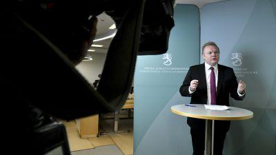 Antti Kurvinen står vid ett bord på en presskonferens.