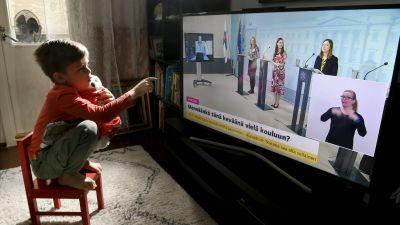 Ett barn sitter i huk på en pall med ett mjukisdjur i famnen och pekar på en teveruta där tre kvinnor står och talar bakom varsitt podium.