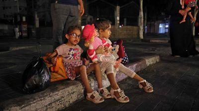 Palestinska barn sitter på en trottoar den 13 maj 2021. Palestinska familjer i Gaza har börjat fly sina hem.