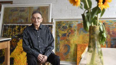 Rafael Wardi sitter framför ett antal tavlor, bredvid en vas med solrosor.