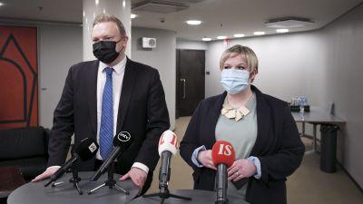 Antti Kurvinen och Annika Saarikko i munskydd står vid ett podium med många mikrofoner.