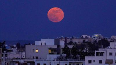 En röd måne mot en blå himmel ovanför vita stenhus.