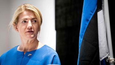 Eva-Maria Liimets står bredvid en estnisk flagga.