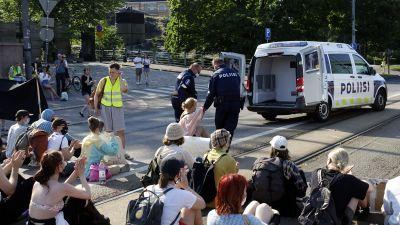Polisen bär bort demonstranter vid Mannerheimvägen i Helsingfors.