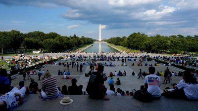 Människor sitter vid Lincolnmonumentet i USA.