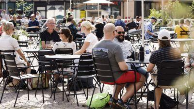 Människor sitter på en uteservering i Helsingfors.