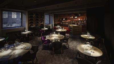 En restaurang med bar och bord och stolar.