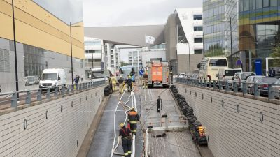 Räddningspersonal går mellan vattenslangar som löper upp till till ett räddningsfordon. Slangarna går längs en ramp ner i en parkeringsgrotta som är översvämmad.