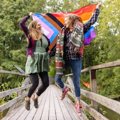 Två kvinnor håller i en flagga i många färger och hoppar upp i luften på en mindre gångbro.