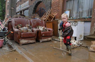 En ung pojke hjälper till med att städa upp efter översvämningarna i Rochefort i Belgien.