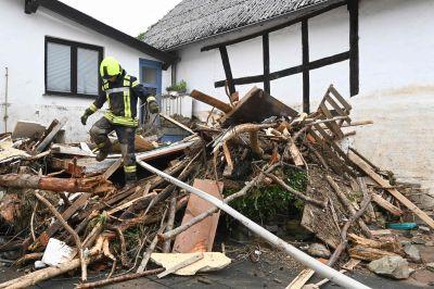 En räddningsarbetare går över skräp som översvämningsvattnet har fört med sig. Bilden är tagen i den tyska staden Schuld.