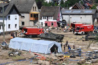 I staden Schuld arbetar man förfullt med att försöka röja upp efter översvämningarna. Flygbild på tält, brandbilar, räddningspersonal, militärfordon och förstörda hus.