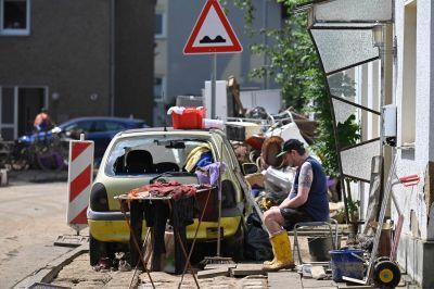 En man sitter på en bänk, omgiven av skräp efter översvämningarna. Bilden är tagen i den tyska staden Arloff.