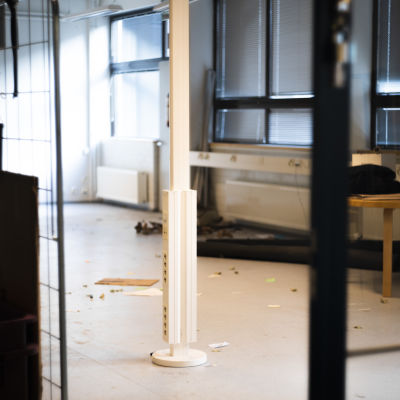 En kontorsbyggnad där saker ligger huller om buller. Byggnaden verkar inte vara i bruk, men lampan är ändå tänd. I rummet syns eluttag och ett bord.