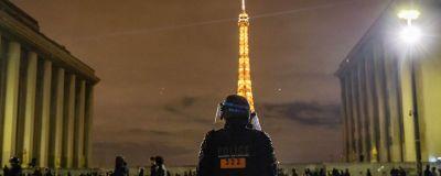 Det är mörkt. En polis står med ryggen mot kameran och skymmer delvis Eiffeltornet i bakgrunden. Människor promenerar förbi..