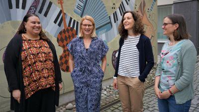 Fyra kvinnor står framför en väggmålning.