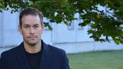 Kim Strandberg, en vit man, står framför ett träd och ett betonghus.