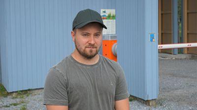 Ung man i keps och grå t-skjorta står framför en blå port.