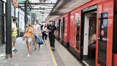 Människor i munskydd står utanför en metro.