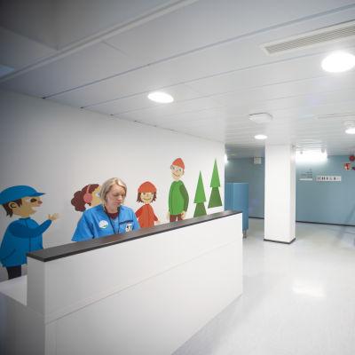 En korridor med en disk. Bakom disken sitter en kvinna med hälsocentralskläder.