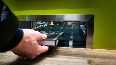 Henkilö palauttaa kirjaa kirjaston palautusautomaattiin.