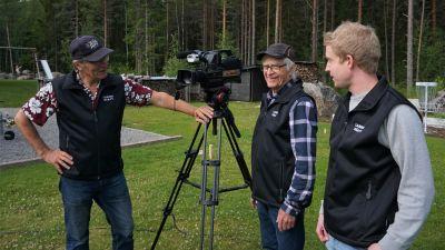 Tre män står runt en videokamera.