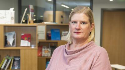 En kvinna i rosa tröja  står framför en bokhylla.