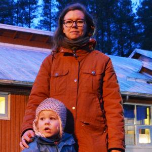 En kvinna i röd jacka står mitt i bild och tittar in i kameran. Hon håller handen på en liten pojkes axel. Han tittar åt vänster, ut ur bilden. Det är mörkt ute. De står framför ett rött trähus. Genom husets glasdörrar syns gult ljus.