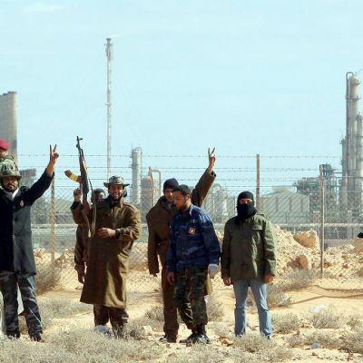 Joukko aseistautuneita miehiä seisoo verkkoaidan edessä avolavauton vieressä. Miehet nostavat käsiään ja aseitaan ilmaan ja näyttävät sormillaan voitonmerkkejä. Taustalla näkyy öljynjalostamon rakennuksia.