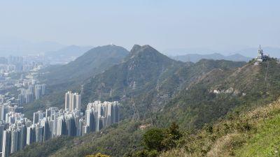 Bild på höga kullar och branter, nedanom dem syns ett hav med skyskrapor.