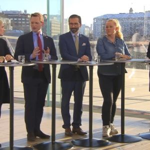 Fem partirepresentanter står vid höga bord och diskuterar valresultatet med allvarliga miner.